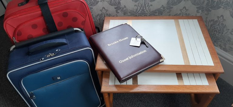 Showing guest information folder, keys & suitcases